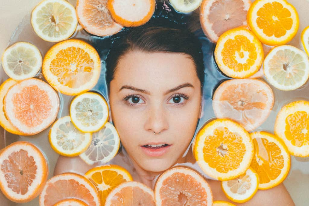 A woman in water surrounded by oranges