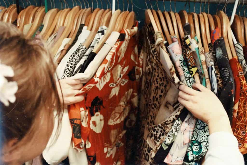 A woman goes through her clothes in her wardrobe