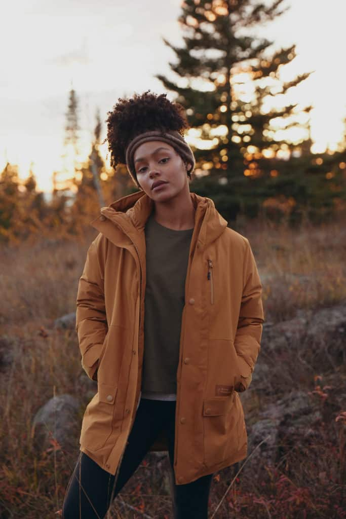 A woman in the woods wearing a brown, climate friendly jacket