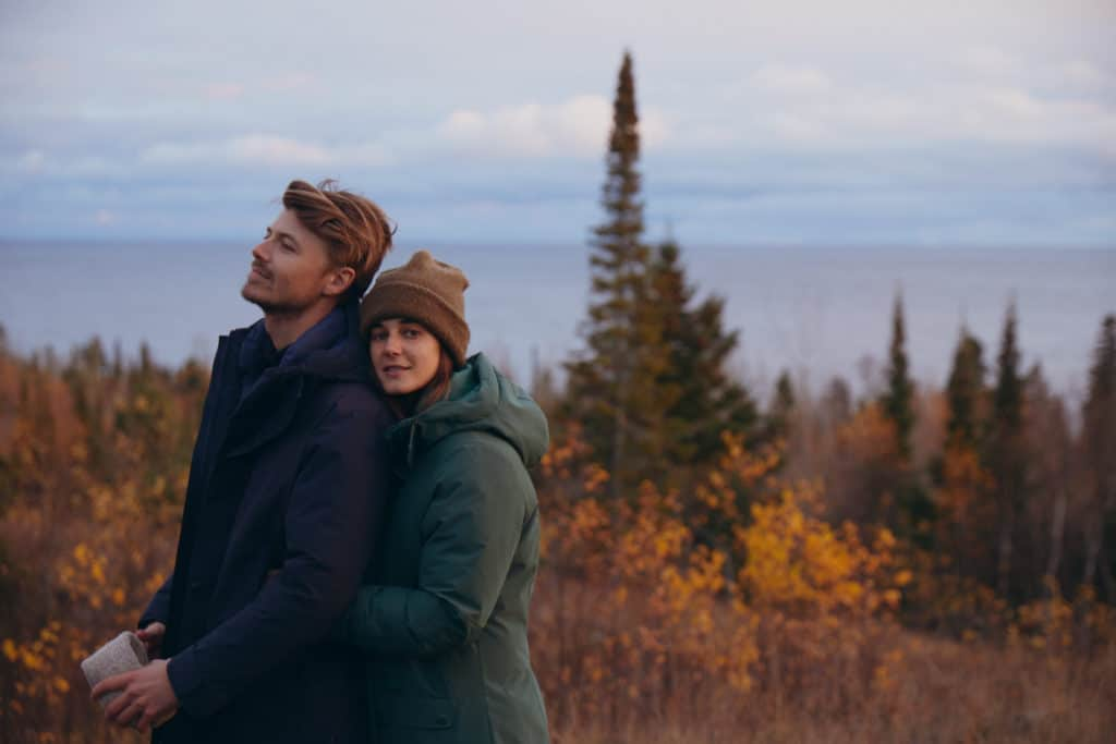 A man and a woman outdoors in winter wearing eco-friendly outdoor clothing