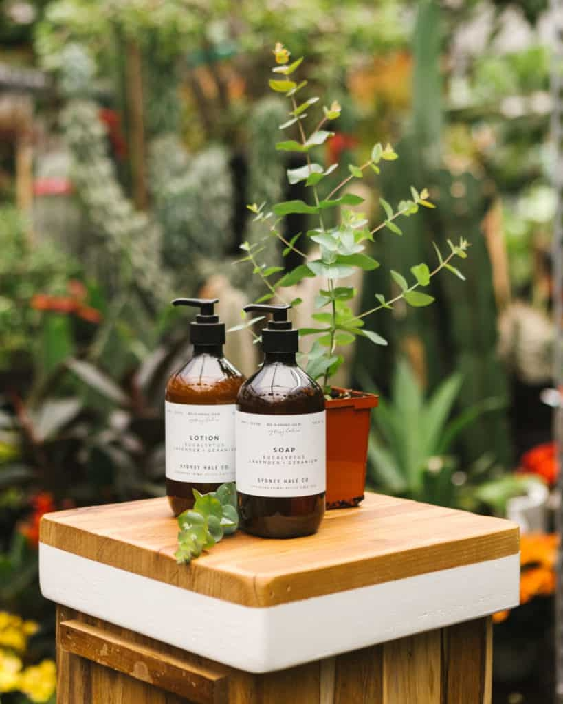 Soap and lotions next to a plant outside