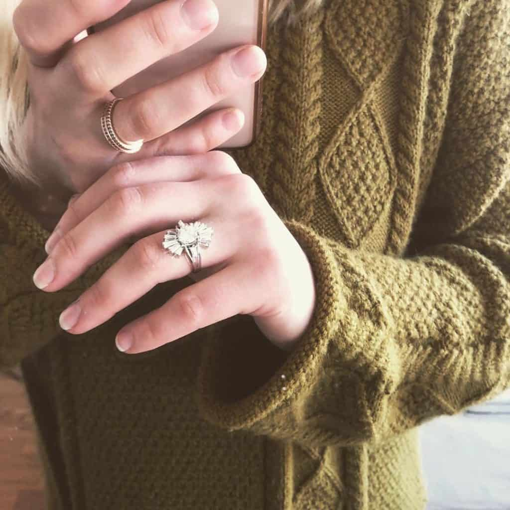 A woman's hands with a ring on each finger made from ethical jewelry