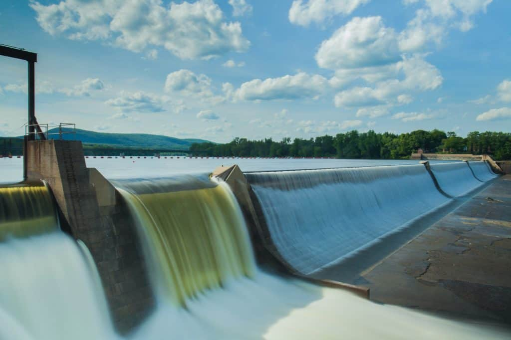a hydropower water dam under white and blue skies