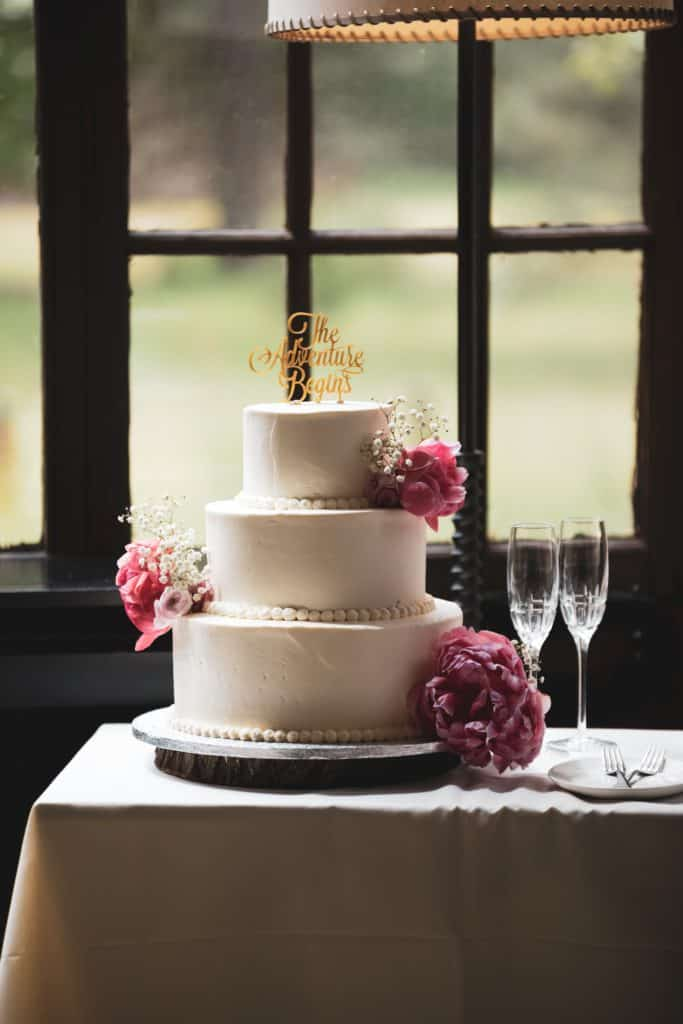 three-tier cake with pink fresh flowers on table beside two champagne flute glasses