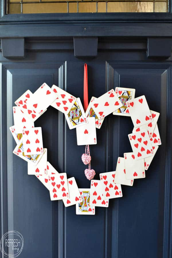 an upcycled wreath made from playing cards hanging on a door